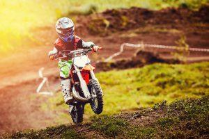 Fotolia 189702926 Subscription Monthly M 300x200 - Racer child on motorcycle participates in motocross cross-country in flight, jumps and takes off on springboard against sky. Concept active extreme rest teenager.